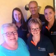 Zahnarzt Andreas Hager und Team mit zufriedener Patientin